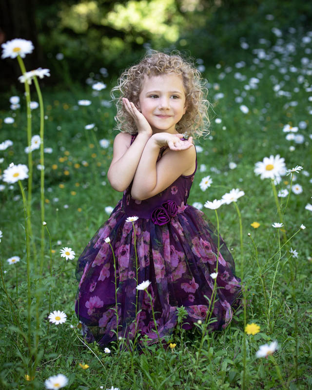 cute girl posing by grass and daisies