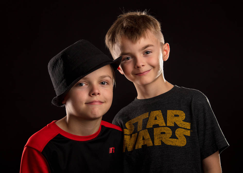 indoor portrait two boys brothers on black